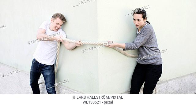 Angry couple pulling a rope from opposite sides of corner of house. Conceptual image of conflict in a relationship, opposing sides and determination