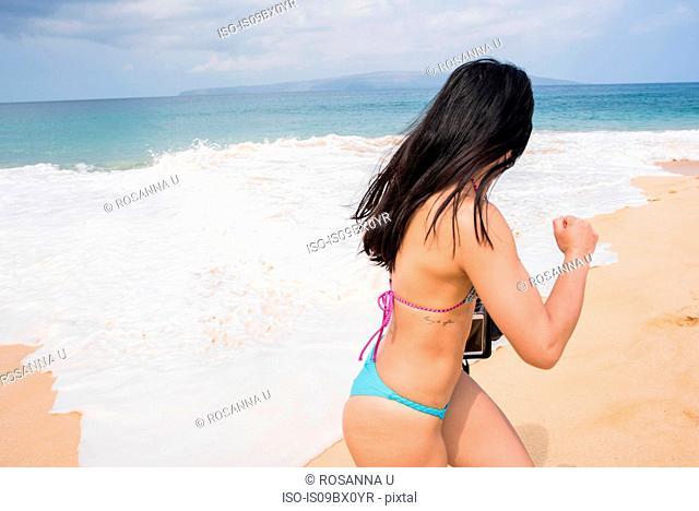Woman running away from sea waves, Makena Beach, Maui, Hawaii