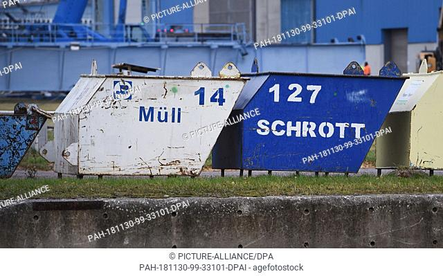 30 November 2018, Mecklenburg-Western Pomerania, Wolgast: Garbage and scrap containers stand in front of the shipyard hall of the Peene shipyard belonging to...