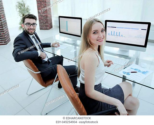 employees of the company work with financial data sitting at the desk