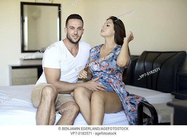 young couple sitting on bed, pregnancy, relationship