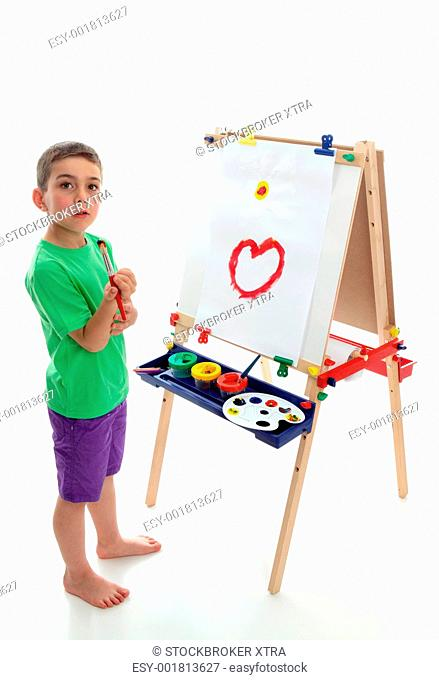 A young boy child stands by an easel with a beginning of a picture painted. White background