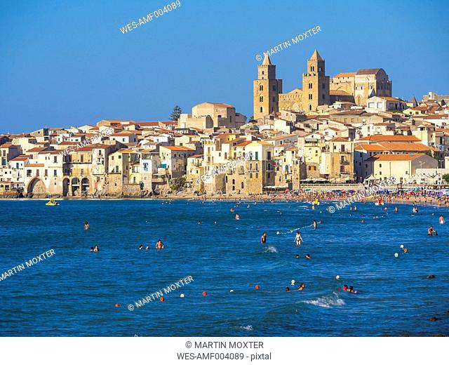 Italy, Sicily, Cefalu, View of Cefalu with Cefalu Cathedral, beach and tourists in water