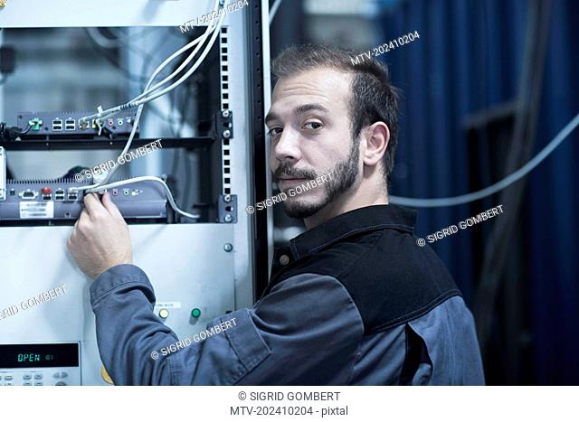 Young male engineer connecting plug in router in technology space, Freiburg Im Breisgau, Baden-Württemberg, Germany
