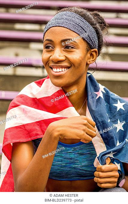 Smiling black athlete wrapped in American flag
