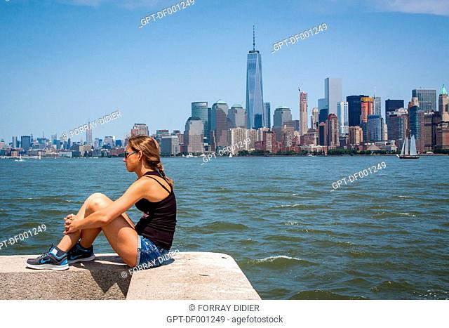 TOURIST SOAKING IN THE SUN ACROSS FROM THE MANHATTAN SKYLINE WITH ONE WORLD TRADE CENTER AND THE EMPIRE STATE BUILDING IN THE BACKGROUND, NEW YORK HARBOR