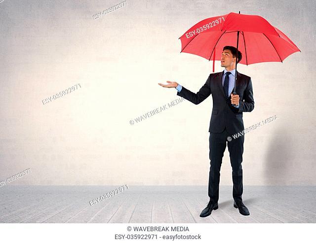 Businessman under umbrella in room