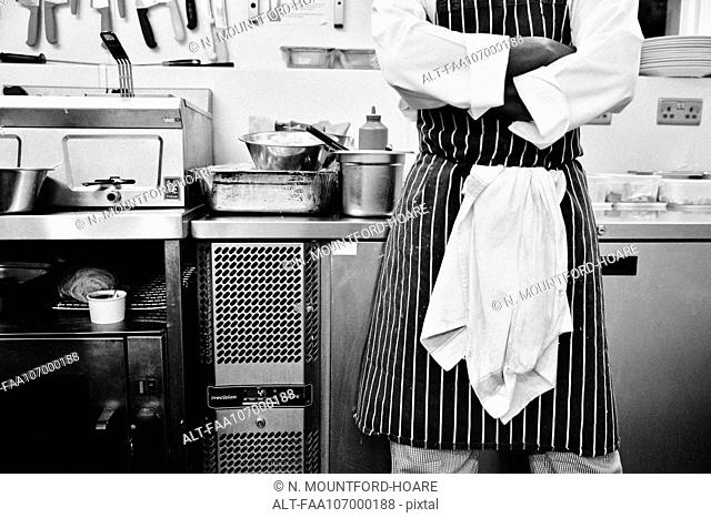 Chef with arms folded standing in commercial kitchen, mid section