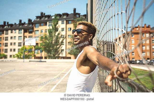 Young man with sunglasses leaning on net of basketball court