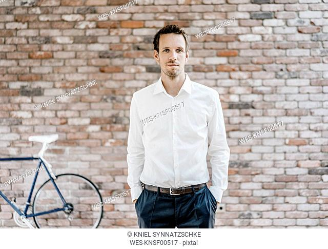Portrait of confident businessman in front of brick wall