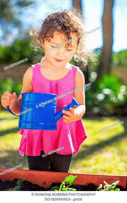 Young girl in garden, holding watering can