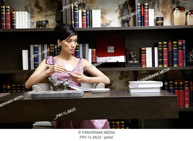 Young woman drinking coffee with bookshelf in background
