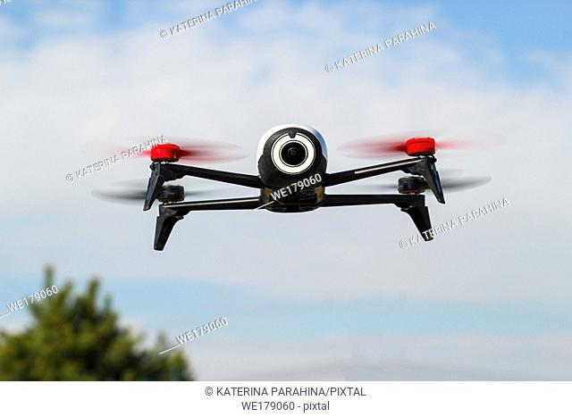 Flying drone with mounted camera in the blue cloudy sky