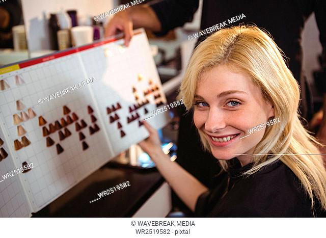 Smiling woman selecting a hair color with stylist at the hair salon