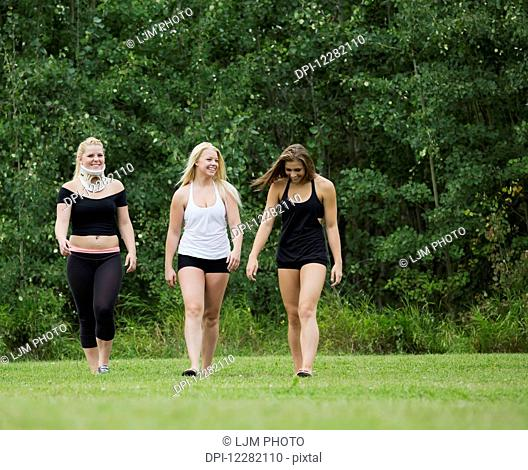 Three young gymnasts walking in a park after practicing their routine; Edmonton, Alberta, Canada