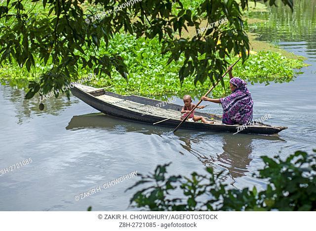 DHAKA, BANGLADESH - AUGUST 05 : A Bangladeshi women going home with her child by boat near Dhaka, Bangladesh on August 05, 2016. .