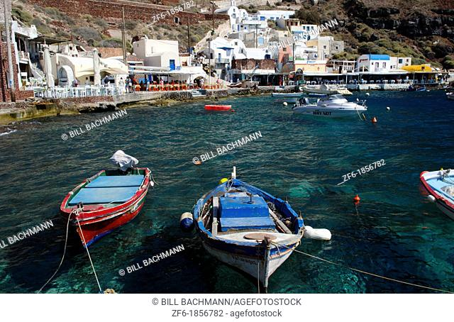 Beautiful harbor with fishing boats at water with Oia above on mountain in Santorini Greece in Greek Islands