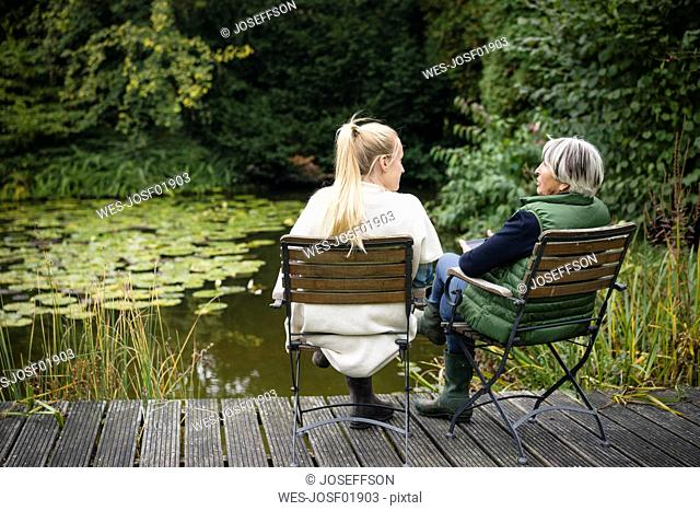 Young woman with her grandmother sitting on jetty at garden pond