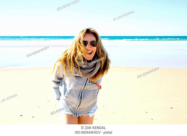 Portrait of mature woman with long blond hair on beach, Conil de la Frontera, Spain