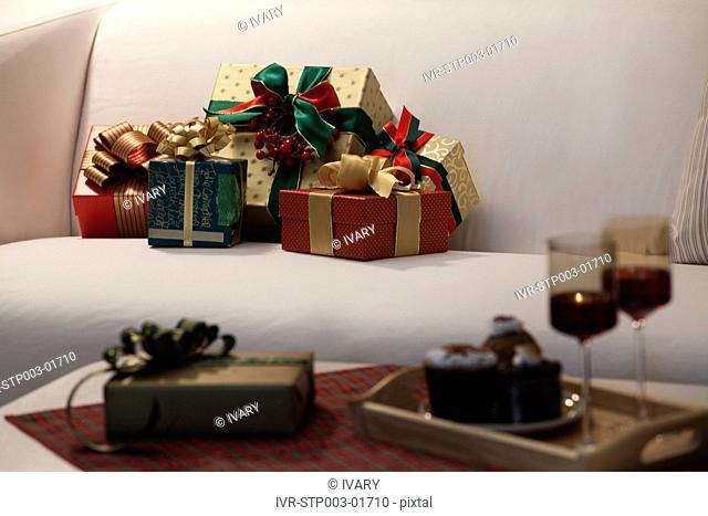 Christmas Gift Boxes On Sofa With Wineglass And Christmas Cake