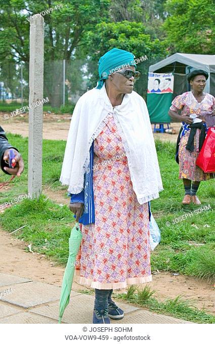 Black woman with green umbrella walking through Zulu village in Zululand, South Africa