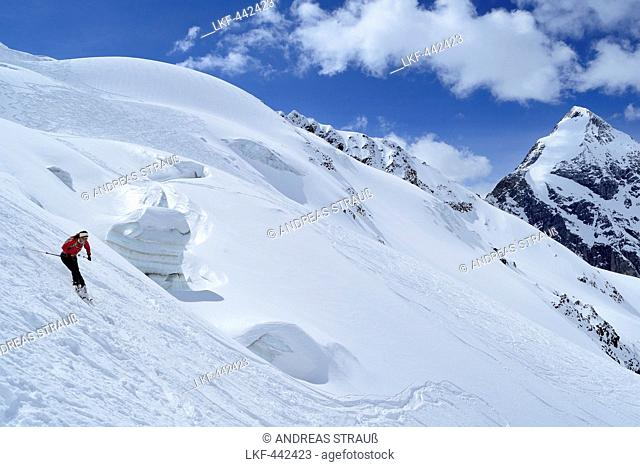 Female backcountry skier downhill skiing in front of Koenigspitze, Monte Cevedale, Ortler range, South Tyrol, Italy