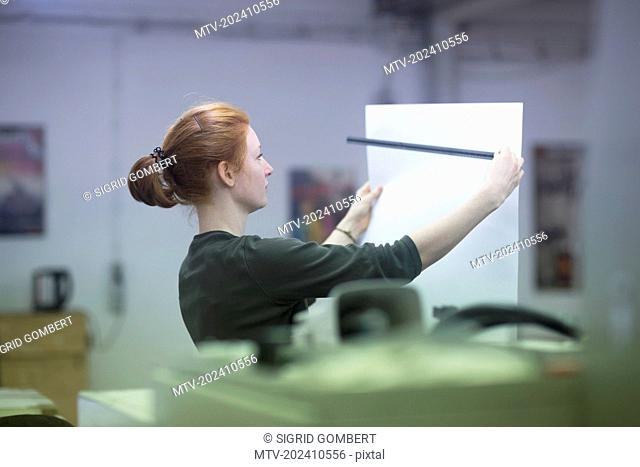 Beautiful worker measuring printouts with ruler