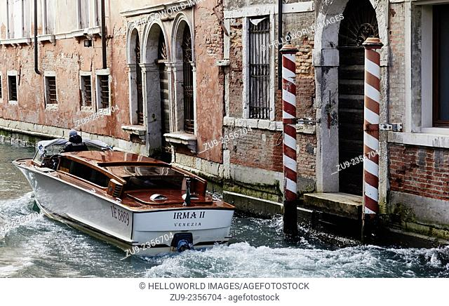 Water taxi speeding along a traditional small canal, Venice, Veneto, Italy, Europe
