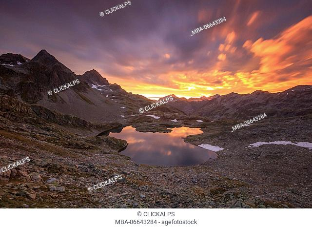 Fiery sky at dawn reflected in Lai Ghiacciato framed by peaks Val Ursaregls Chiavenna Valley Valtellina Lombardy Italy Europe