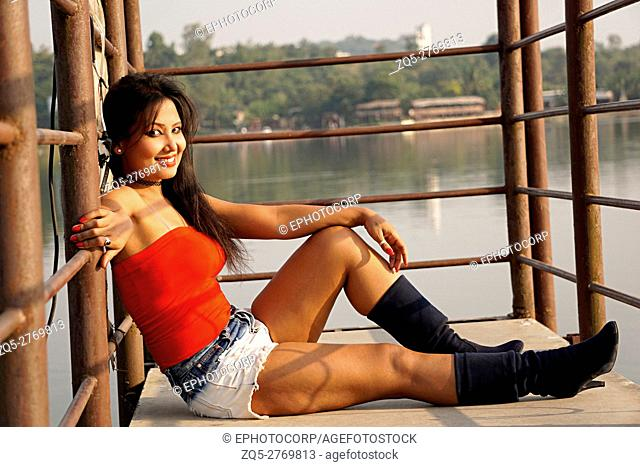 Young Woman in white shorts, red top and boots sitting relaxed and posing for camera. Pune, Maharashtra