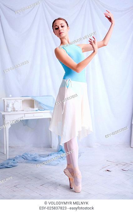Professional ballerina dancer posing against the white dressing room