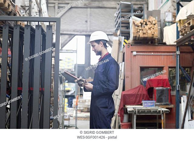 Warehouseman in storehouse holding clipboard