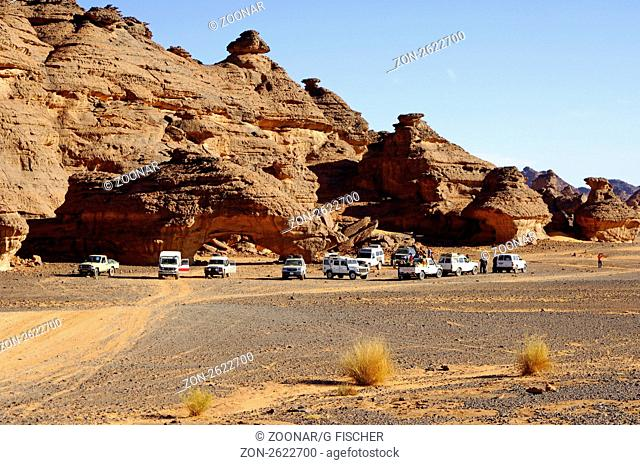 Mehrere Geländewagen parken am Fuss eines bizarren Felsgebildes im Akakus-Gebirge, Sahara, Libyen / Several off-road vehicles parking at the foot of a bizarre...