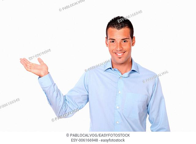 Portrait of an attractive man holding out his right palm while smiling and looking at you on isolated background - copyspace