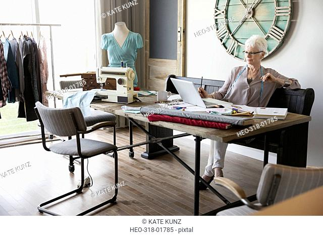 Senior woman seamstress working at laptop in home office