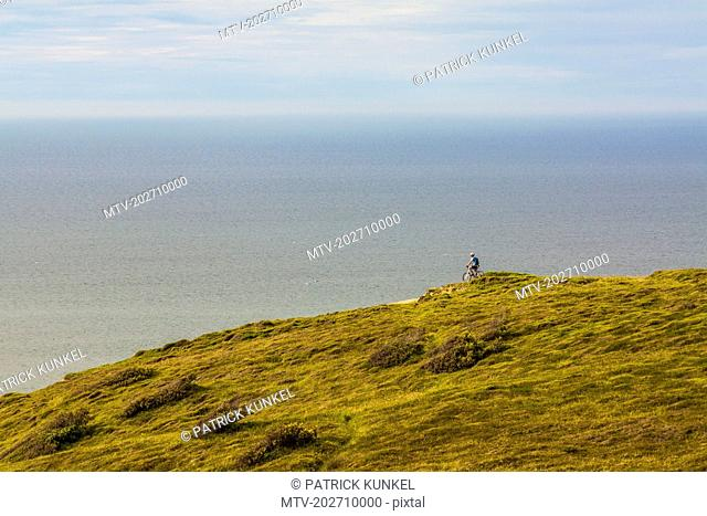Mountain biker admiring seascape from green hill
