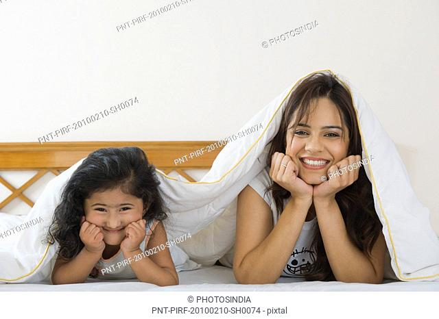 Woman with her daughter lying on the bed