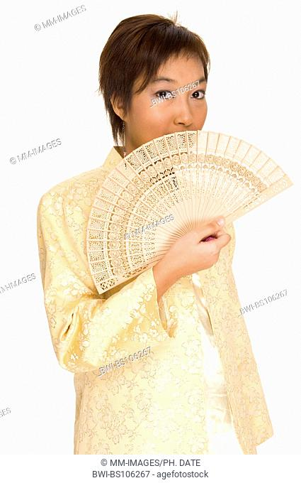 A young Malay woman wearing a traditional outfit holds a wooden fan