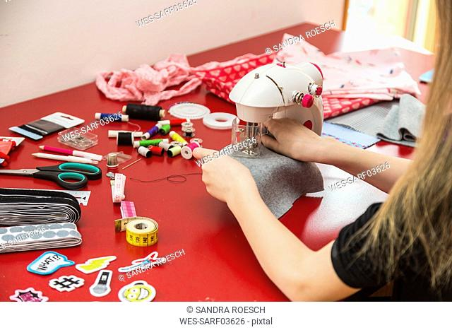 Close-up of girl using sewing machine