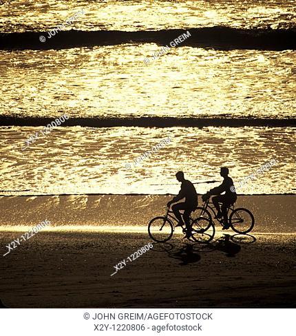 Silhouette of couple biking along the beach, Cape Cod