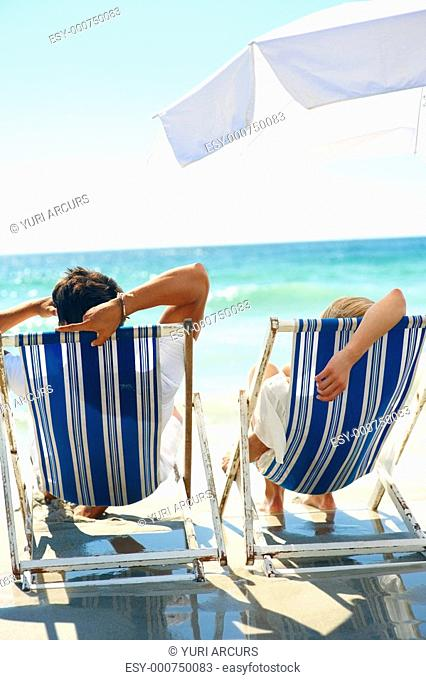 Rear view of a couple on a deck chair enjoying by the beach