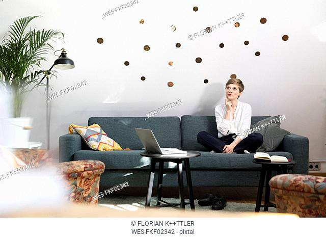 Woman with laptop sitting on couch in modern office