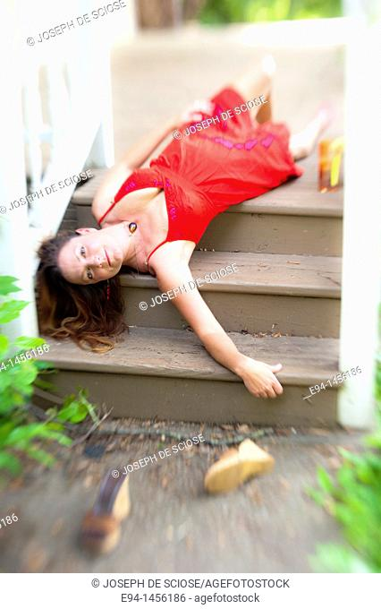 A 36 year old brunette woman in a red summer dress lying on her back on porch steps looking directly at camera