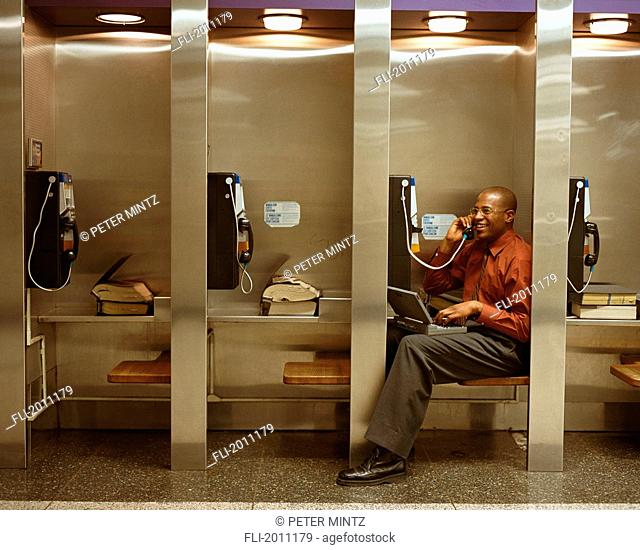 Fv3208, Peter Mintz; Businessman Talking On Payphone In Row Of Phones, Using Laptop