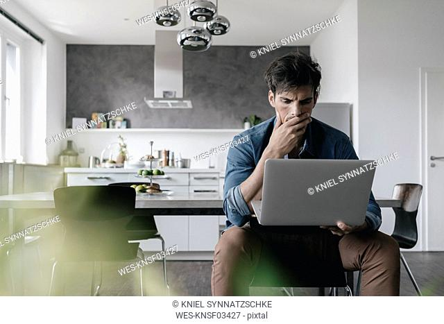 Young man using laptop in the kitchen