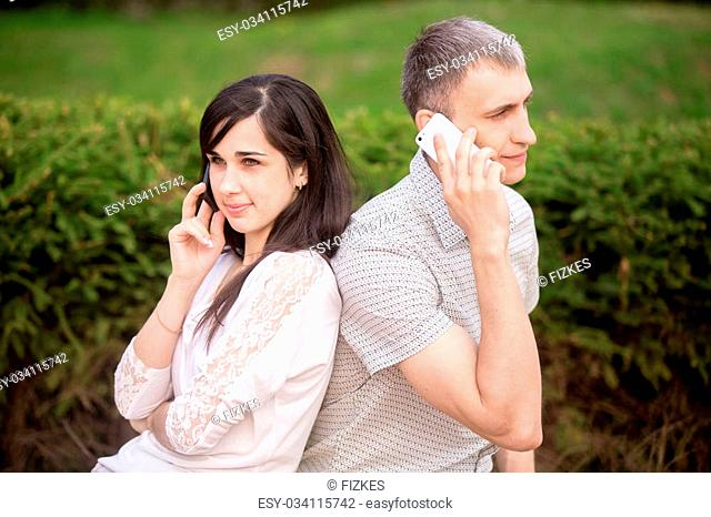 Young couple sitting back to back on park bench holding cellphones in hands, making call, not looking at each other
