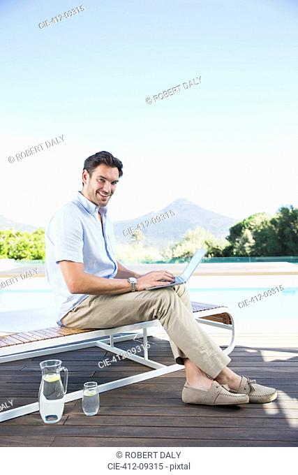 Man using laptop on lounge chair at poolside