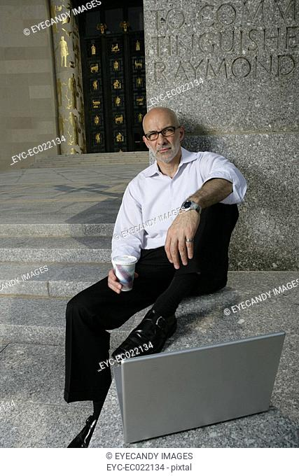 mature man resting outside with laptop