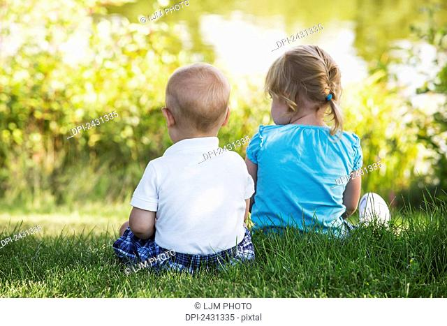 Young brother and sister sitting together beside a lake in a park; Edmonton, Alberta, Canada