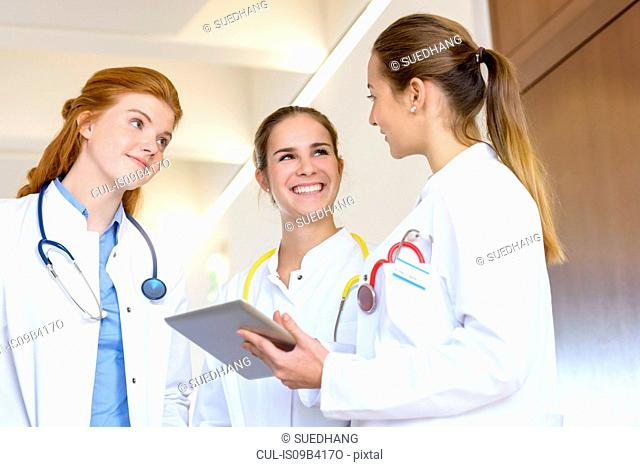Three young female doctors with digital tablet having discussion in hospital